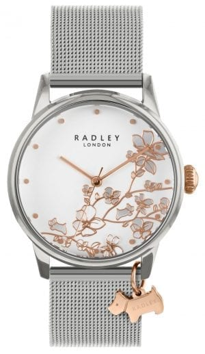 Radley Linear Flower Silver Stainless Steel Mesh Quartz Ladies Watch RY4347This Radley Linear Flower Silver Stainless Steel Mesh Quartz Ladies Watch RY4347 makes for a luxurious addition to ones wrist. A predominately white dial features a beautiful floral pattern as the collection would suggest. Surrounding the dial is a silver stainless steel case with mineral glass sat ontop. Additionally, a silver stainless steel mesh bracelet can then be fastened using a fold over deployment.This watch has a water resistance of 30 metres, making it suitable for light splashes.Key Features:Black Leather Strap Floral PatternSilver Stainless Steel Case White DialQuartz MovementFold Over DeploymentSilver Stainless Steel Mesh BraceletAnalogue DisplayDog CharmThe Brand: RadleyWe are a London born brand that has a passion for crafting beautiful handbags and accessories that women love. Our approach is simple – to create the perfect combination of style on the outside and functionality on the inside. To achieve this we blend creative design, quality materials and immaculate craftsmanship, not forgetting plenty of personality to finish. We hope you enjoy exploring our world…