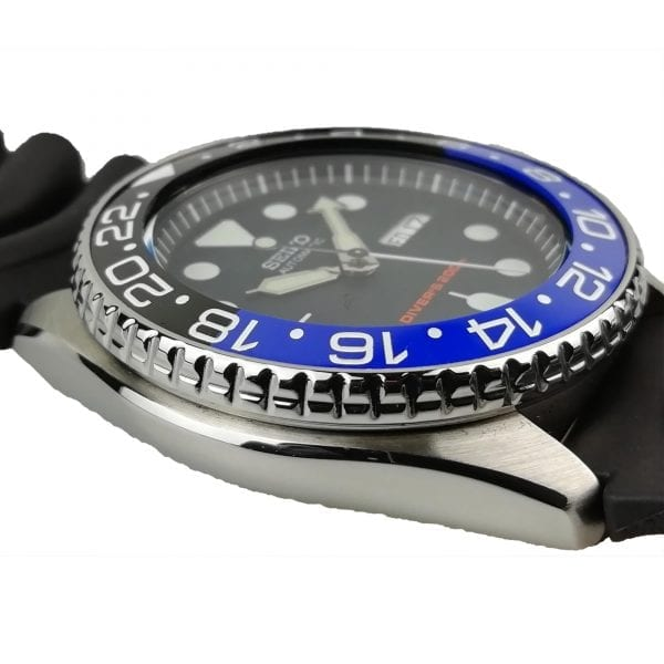 Seiko Customised Diver's Automatic Batman Rubber Strap Stainless Steel Case Men's WatchThis Seiko Customised Diver's Automatic Batman Rubber Strap Stainless Steel Case Men's Watch takes inspiration from the crime-stopping hero, Batman. Firstly, a customised black and blue bezel has been delicately placed on-top of a stainless steel case by our in house experts at Watchnation. Also, a black dial is complimented by white indexes and hands, of which are powered by a precise 21 jewel automatic movement. Furthermore, a day and date window can be located at the 3 o'clock position with the ever present Seiko logo at 12. Moreover, a crown can be found recessed at the 4 o'clock position to prevent any knocks or damage to it. Then, a black rubber strap can be fastened using a standard buckle.Finally, this watch has a water resistance of 200 metres, making it suitable for diving.Key Features:Seiko 7S26 Calibre21 Jewels40 Hour Power Reserve Automatic MovementUnidirectional Rotating BezelLuminous Hands & MarkersRobust Black Rubber StrapHardlex Crystal GlassDay/Date Window200m Water ResistantThe Brand: SeikoCeaseless determination to innovate in every aspect of the watchmaker's art is what defines Seiko's 135-year history. By embracing this ethos, Seiko has been responsible for a string of industry-leading advances in the technology of time. Notably, the creation of the world's first quartz watch in 1969. Or equally impressive the creation of the world's first TV watch in 1982. And even more relevant today, with our abhorrent use of non-renewable energy sources, Seiko's Kinetic. The listed technological developments serve as evidence to illustrate the revolutionary impact which Seiko has had on the watchmaking world. They are also remarkably unique in that they manufacture every aspect of every watch in-house.If you have any questions pleaseclick hereClick here to join ourfacebookandInstagram!