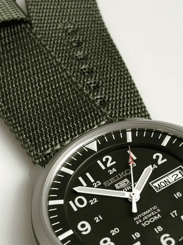 Seiko 5 Sports Automatic Military Khaki Green NATO Canvas Strap Men's WatchDriven by a 23 jewel automatic movement, this Seiko 5 Sports Automatic Military Khaki Green NATO Canvas Strap Men's Watch pairs legendary Seiko 5 reliability and precision with military style khaki green canvas strap. the green colour scheme is continued within the dial with a Seiko 5 logo sitting below the 12 o'clock index and a day and date window taking the place of the 3 o'clock index. Around the edge of the dial are indexes for both 12 and 24 hour displays, suiting the needs of both. This simplistic dial is protected by a silver stainless steel case and hardlex crystal glass.This timepiece has a water resistancy of 100 metres, making it suitable for swimming but should not be submerged to any considerable amount.Key Features:Seiko 7S26 Calibre Engine23 Jewel Automatic MovementOpen Case BackDay/Date WindowKhaki Green Canvas Strap100m Water ResistantDark Green DialSilver Stainless Steel Case12/24 Hour DisplayAnalogue DisplayHardlex CrystalPull/Push CrownBuckle Clasp The Family:The Seiko 5 family has set the standard in affordable, rugged and stylish watches since 1963. They incorporate simplicity, but seriousness. The name of the Seiko 5 derives from its five key attributes, which Seiko promised to include in every watch that belonged to the family. They are: automatic winding, displaying the day and date in a single window, water resistance, a recessed crown at the 4 o'clock position and a durable metal bracelet. 1963 marked the year that the Seiko 5 acted as a catalyst in the horological revolution in automatic watchmaking. Even after being in the market for over 50 years, albeit the Seiko 5 remains as cool and relevant as ever. Though this serves as proof that expert craftsmanship and elegant design will never go out of fashion.The Brand: SeikoCeaseless determination to innovate in every aspect of the watchmaker's art is what defines Seiko's 135-year history. By embracing this ethos, Seiko has been responsible for a string of industry-leading advances in the technology of time. Notably, the creation of the world's first quartz watch in 1969. Or equally impressive the creation of the world's first TV watch in 1982. And even more relevant today, with our abhorrent use of non-renewable energy sources, Seiko's Kinetic. This watch had the ability to generate its own power from the movement of the wearer, it was released in 1988. The listed technological developments serve as evidence to illustrate the revolutionary impact which Seiko has had on the watchmaking world. They are also remarkably unique in that they manufacture every aspect of every watch in-house. They even grow their own quartz crystals and sapphires, hence why Seiko are renowned for being watchmaking experts.If you have any questions please click hereClick here to join our facebook and Instagram!