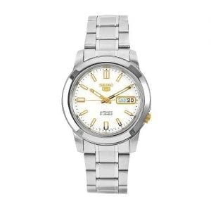 Seiko 5 Automatic Silver Stainless Steel Mens Watch SNKK07K1 39mmDriven by a 21-jewel automatic movement, this Seiko 5 Automatic Silver Stainless Steel Mens Watch (SNKK07K1) features a silver/white dial, a stainless steel case and bracelet, and a day and date window. Key Features:Automatic MovementStainless Steel Case/BraceletCaliber 7S2621 JewelsSilver/White DialAnalog DisplayLuminous Hands/MarkersDay/Date DisplayFold Over Clasp30m Water Resistant The Family: Seiko 5The Seiko 5 family has set the standard in affordable, rugged and stylish watches since 1963. Designed to be simple but serious, the Seiko 5 is so-called due to its five key attributes: automatic winding, displaying the day and date in a single window, water resistance, a recessed crown at the 4 o'clock position and a durable metal bracelet. Released in order to meet the demands of the revolutionary baby-boomer generation, the Seiko 5 collection is just as popular to this day, proof that expert craftsmanship and elegant design will never go out of fashion. The Brand: SeikoSeiko's 135-year history has been marked by a ceaseless determination to innovate in every aspect of the watchmaker's art. By embracing this mantra, Seiko has been responsible for a string of industry-leading advances in the technology of time, such as the world's first quartz watch, the world's first TV watch, and the Seiko Kinetic, the first watch ever to generate its own electricity from the movement of the wearer. Seiko are unique in that they manufacture every aspect of every watch in-house, with this ruthless pursuit of perfection even including growing their own quartz crystals and sapphires.